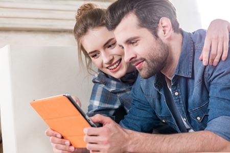 Junges Paar liest die Vorteile und Nachteile